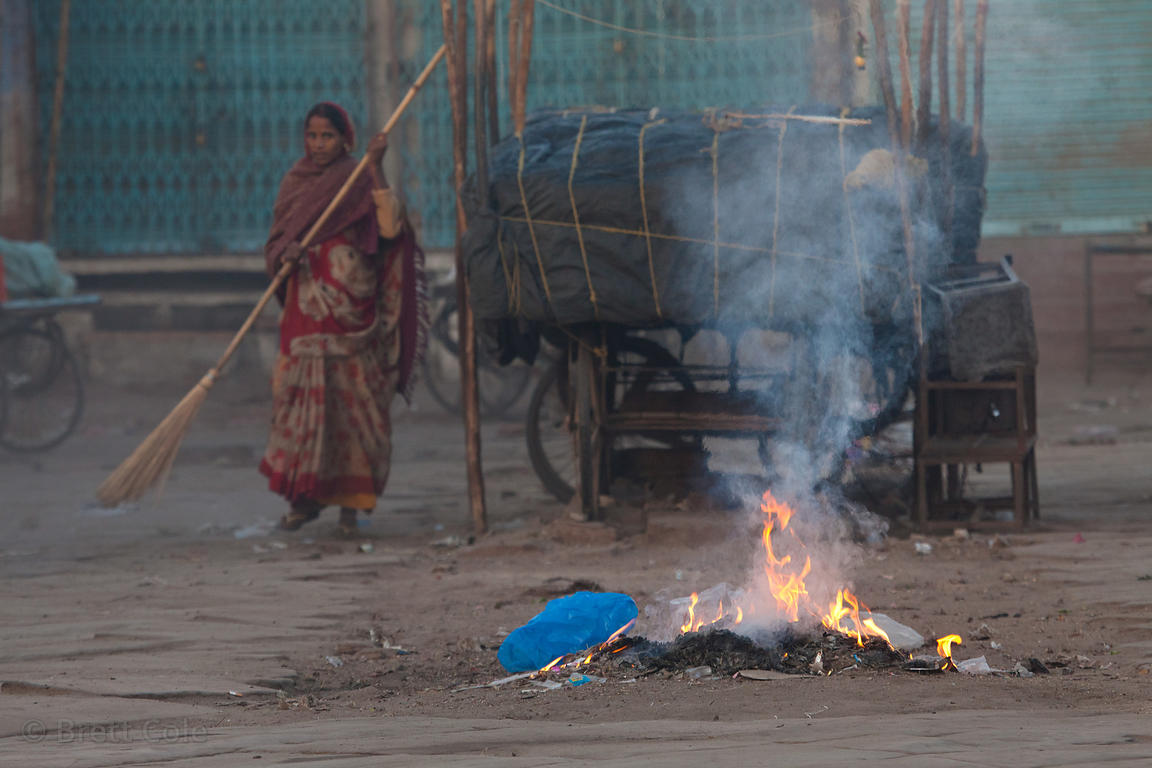 A woman sweeps the streets at sunrise admidst burning trash piles, Jodhpur, Rajasthan, India