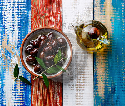 Kalamata olives and Olive oil on wooden background