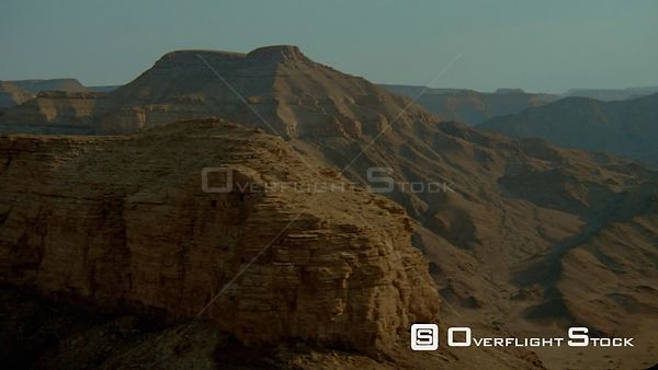 Aerial lens flare along dark weathered cliff face to end of rocky outcrop up and over top, wide shot sides of mountains curvi...