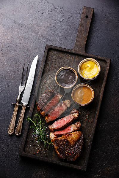 Sliced grilled Rib eye steak and three different sauces: Pepper sauce, Mustard and Barbecue with knife and fork carving set on dark background