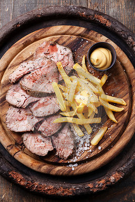 Roast beef with Salted french fries on cutting board