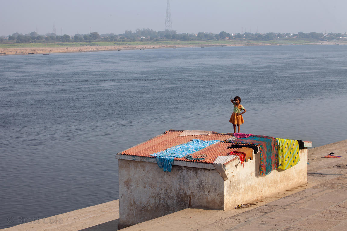 A girl helps her family do laundry along the Ganges River, Varansasi, India.