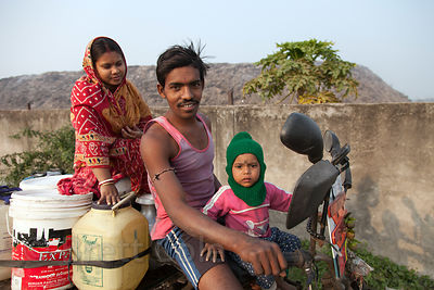 A farming family on an old three-wheel motorcycle pass in front of the Dhapa Dumping Grounds, the primary landfill for Kolkat...