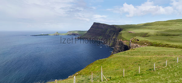 Sea cliffs of Ramasaig with Neist Point in the distance. Isle of Skye, Scotland, UK.