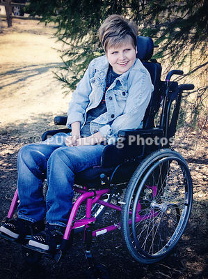 Teenage girl sitting in a wheelchair under a tree in a park