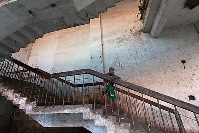 Children play cricket in the stairwell of an abandoned building, Newmarket, Kolkata, India.