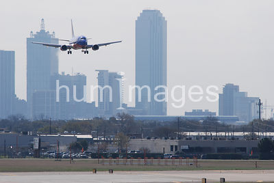 Southwest Airlines jet plane landing with downtown Dallas skyline in background