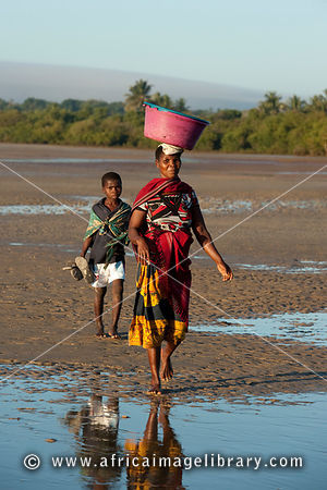 Woman and boy walking on the beach, Vilanculos, Mozambique