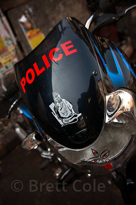 A police motorcycle with a decal of Baba Lokenath on the windshield, Shyambazar, Kolkata, India.