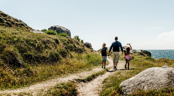 Father and two children walking on Hammerknuden on Bornholm, Denmark 2
