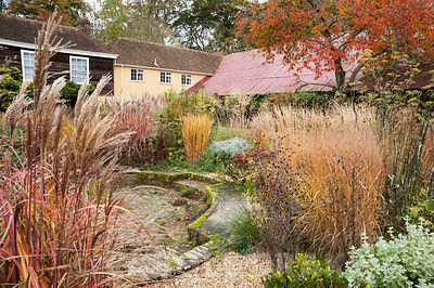 Central circular bed in the walled garden is a colourful mix of grasses, herbaceous perennials such as bronze fennel and ever...