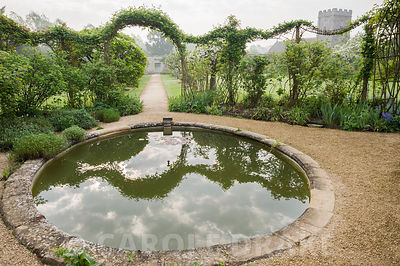 Circular pond in the Walled Garden surrounded by rambling roses trained over metal arches. Rousham House, Bicester, Oxon, UK
