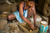 India - Swamimalai - A craftsman moulds local clay around the wax image of a diety to be cast in bronze
