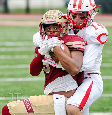 Coe College's Demetrius Harper (5) is wrapped up by Central's Danny Anderson (14) after a catch and run during the first half...