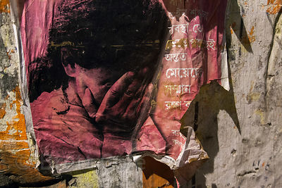 A poster discouraging violence against woman hangs on a wall in Sovabazar, Kolkata, India.