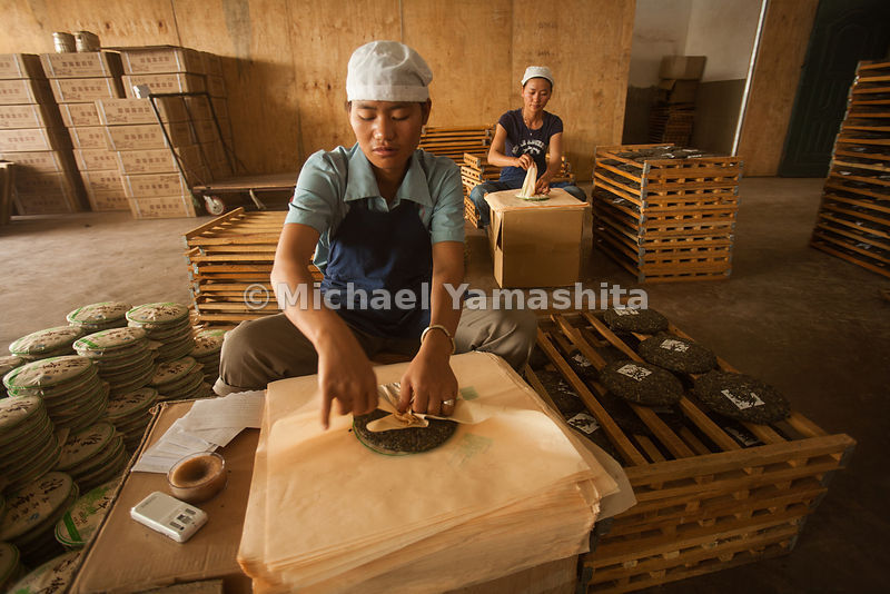 Workers wrap cakes of puer tea in paper at the Riu Xiang Tea Factory in Manghai, Yunnan.