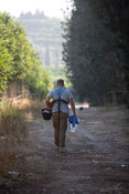 Operators walk to their search areas in an orchard in Al Basouriah, South Lebanon