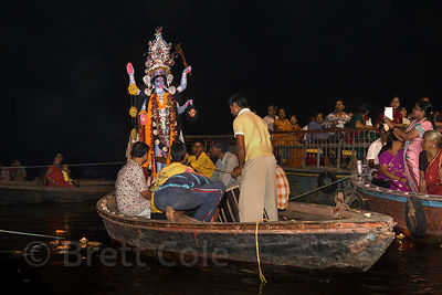 A family prepares to immerse their idol of Kali in the Ganges River during the Kali Mutri festival, Dashashwamedh Ghat, Varanasi, India