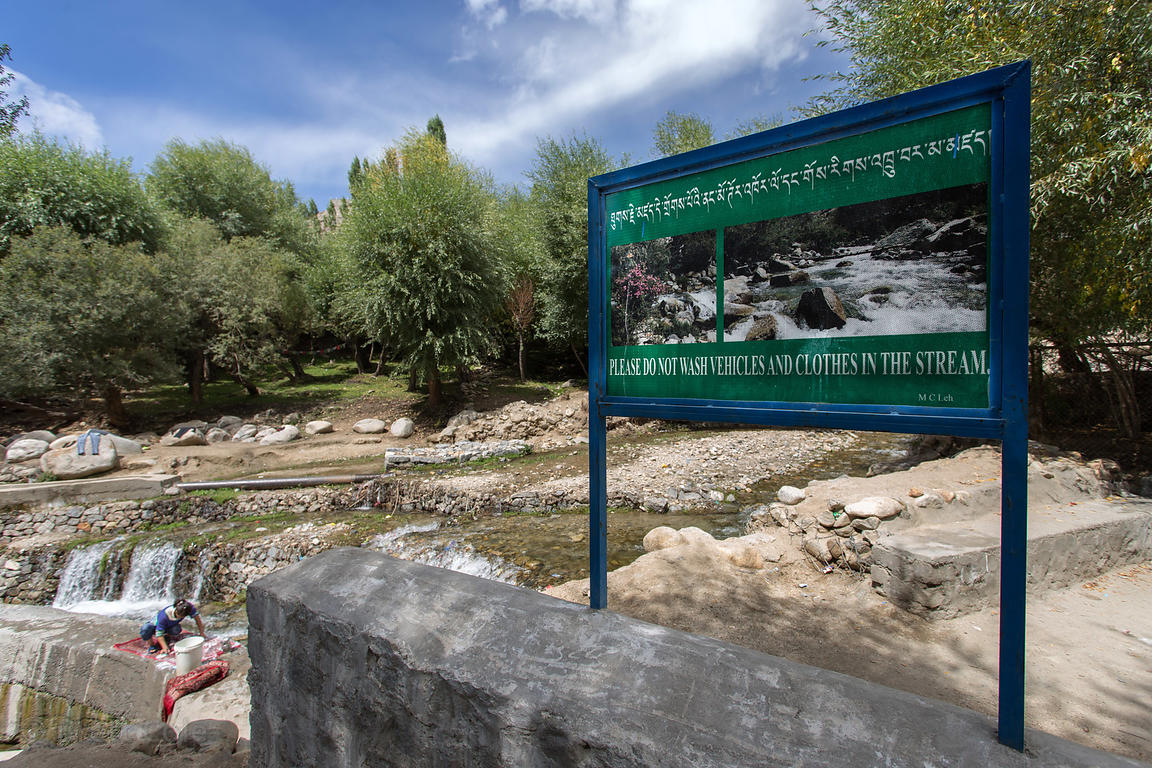A woman washes clothes in a creek in upper Changspa under a sign prohibiting washing of clothes in the creek, Leh, Ladakh, India