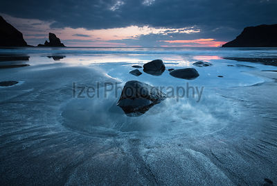 A group of large boulders in a rock pool at Talisker Bay at sunset, Isle of Skye, Scotland.