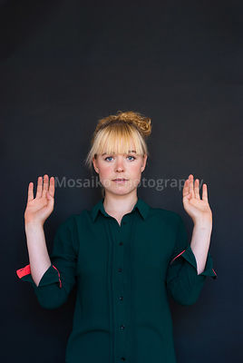 young pretty woman with hands up - studio shot - black background