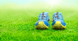 Blue and yellow trainers on a Green Grass and garden foliage background.