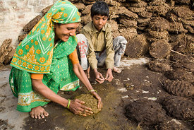 Anuj Kumar and his mother, Chandra make cow dung cakes for fuel