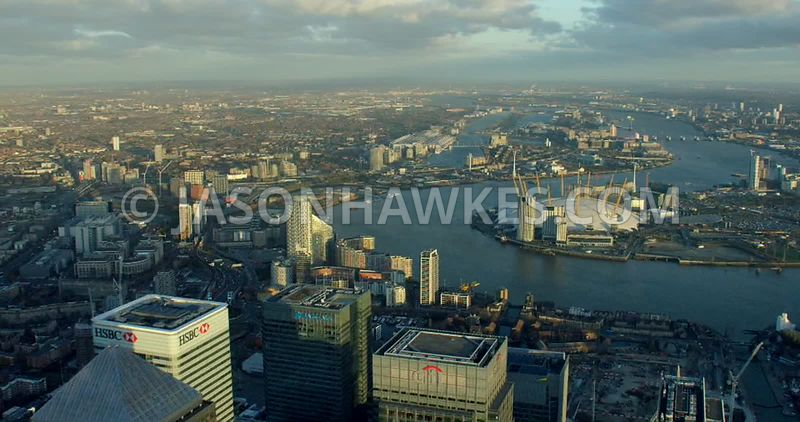 Aerial footage across the skyscrapers of Canary Wharf looking to the O2 Arena and the Royal Docks