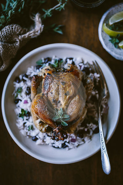 A Cuban Roasted game hen served on black bean rice is photographed from the top view.