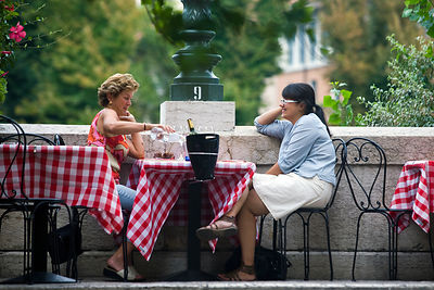Italy - Verona - Two women talk outside a restaurant