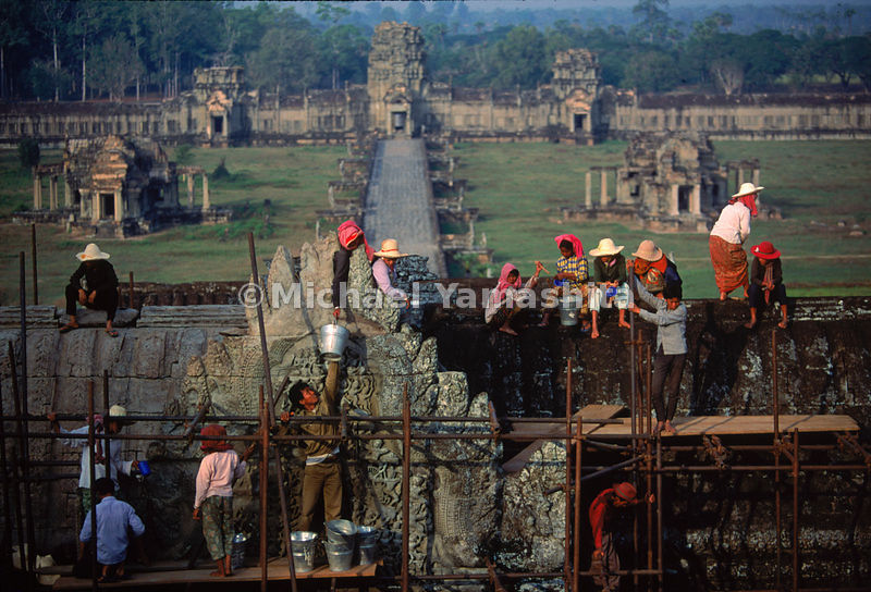 Workers, reclaiming the great temple from the ravages of time and war, scour the front facade of Angkor Wat, as part of a Uni...