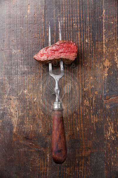Piece of beef steak on meat fork on wooden background