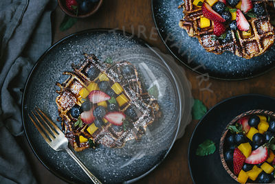 A plate of brioche waffles are topped off with fruit and dusted with powdered sugar photographed from the top view.