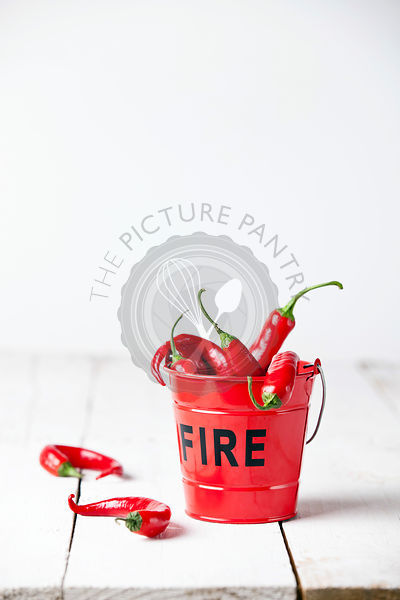 Red chili peppers in fire bucket on white