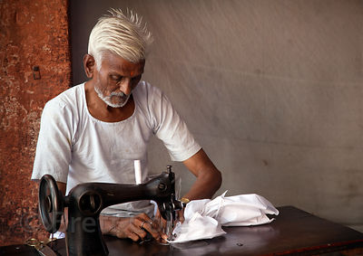 An elderly tailor at work in Jaipur, Rajasthan, India