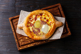 Georgian cheese pastry Ajarian Khachapuri serving size on burned black wooden background
