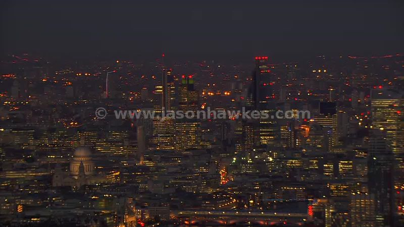 Aerial footage of St Paul's Cathedral, the City and the London Eye at night, London