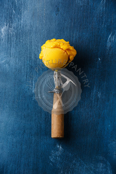 Sorbet mango ice cream ball in scoop on blue background