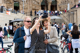 Tourists taking selfies in front of Sagrada Família, a church built by the renowned architect Antoni Gaudí in Barcelona, Spain.