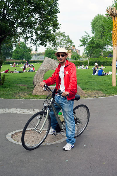 UK - London - A fashionably dressed young Asian man on a bicycle near Brick Lane
