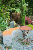Metallic bench and table surrounded by strong foliage plants including pencil cypress, Cupressus sempervirens, acer and tree ...