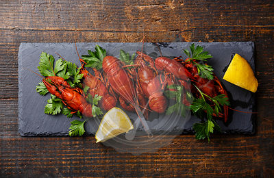 Red boiled crayfish with lemon serving size on stone slate on wooden background