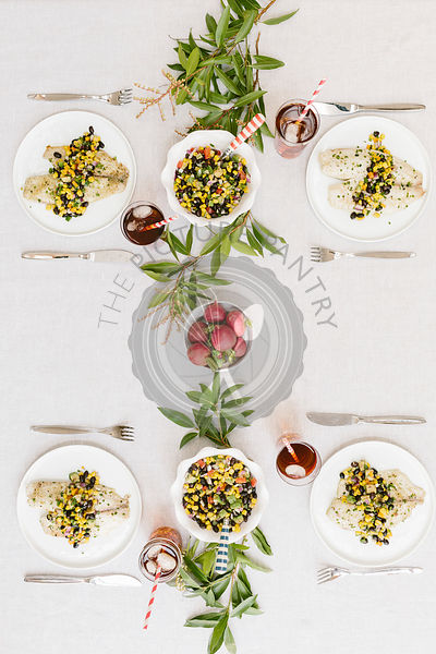 A summery (happy & bright) tablesetting with a portion of Baked Lime and Olive oil tilapia with black bean salsa served on ea...