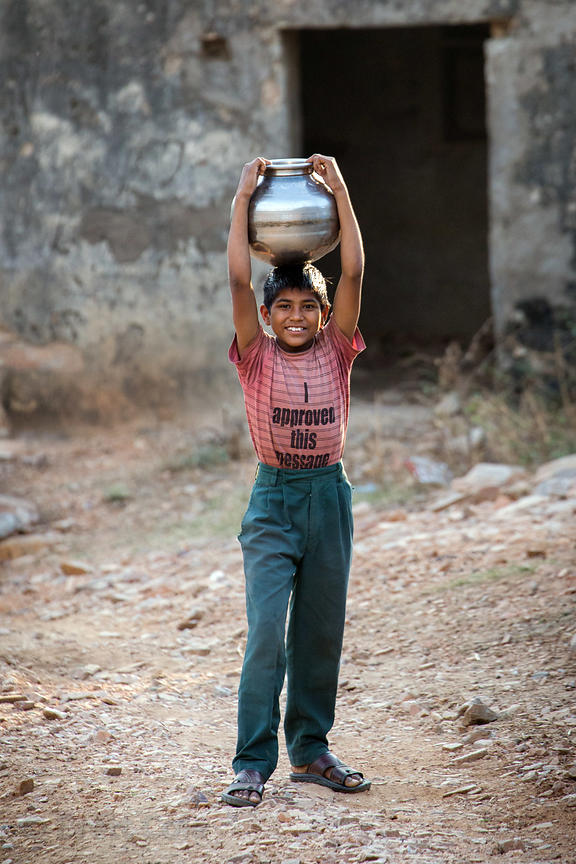 A boy carries a metal water pot on his head, Kharekhari village, Rajasthan, India