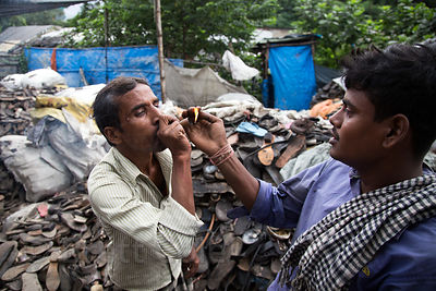 Recycling workers light a tobacco pipe, Dhapa, Kolkata, India