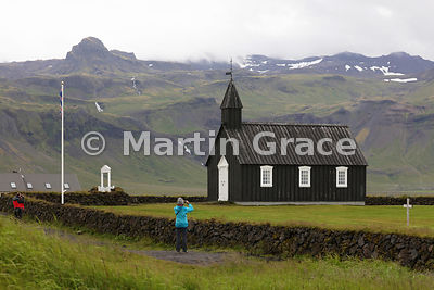 Tourists photographing Budir Church, Snaefellsnes, Vesturland - one of the oldest wooden churches in Iceland
