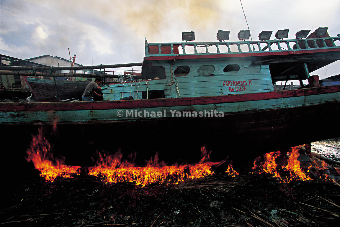 A commercial fishing boat burns from the base while ashore.