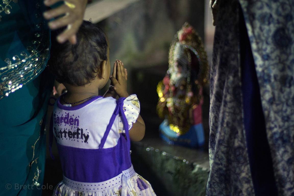 A toddler girl prays to her family's idol of the goddess Durga along the Hooghly River during the Durga Puja festival, Babugh...