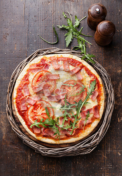 Italian pizza with ham and arugula leaves on wooden table