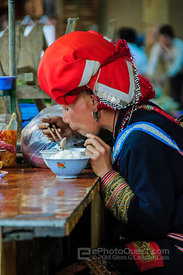 Red Zao Woman Eating in Market